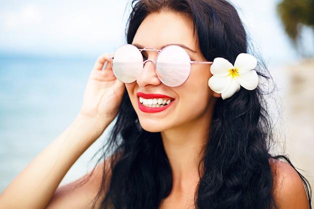 Portrait d'été est jolie fille brune posant sur la plage parfaite de l'île tropicale solitaire, voyagez et profitez de vacances, bikini bleu vif et lunettes de soleil.