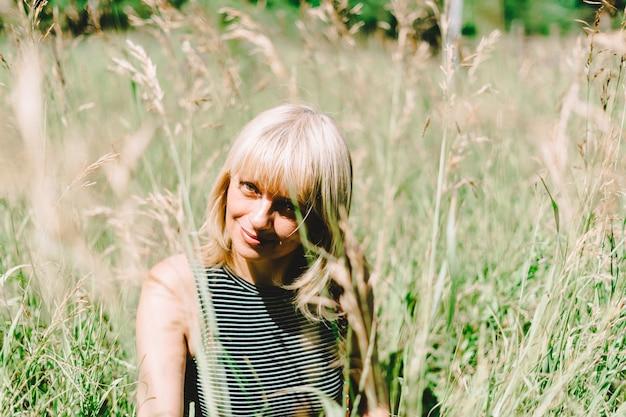 Portrait d'été d'une femme blonde adulte mature assise dans une herbe par une journée ensoleillée dans le pré