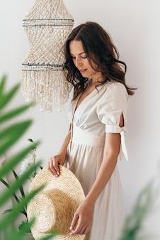 Portrait d'été d'une jeune femme avec un chapeau de paille à la main à la maison.