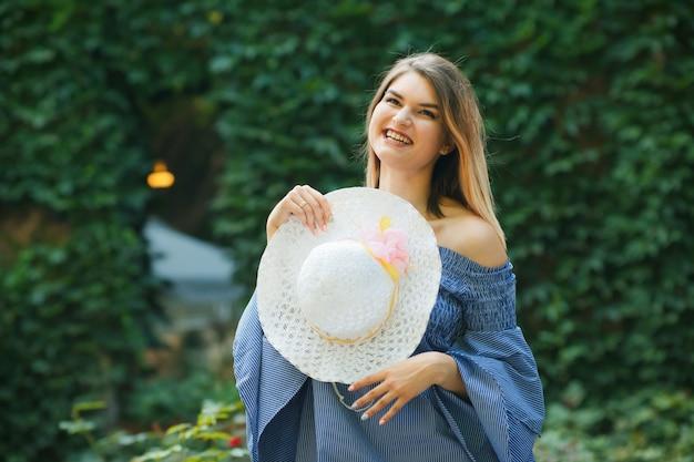 Portrait d'été d'une jeune femme joyeuse avec chapeau et robe sur un arrière-plan flou d'un buisson vert à l'extérieur