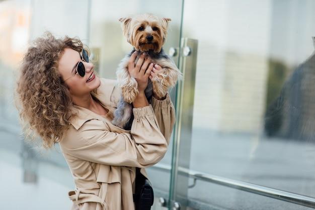 Portrait d'été d'une jeune femme en vêtements nus sur la nature avec un chien de race chihuahua. joli concept.