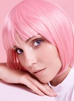 Portrait d'été lumineux d'une fille magnifique et positive aux cheveux roses posant sur studio coloré