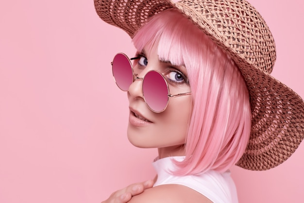 Portrait d'été lumineux d'une fille magnifique et positive avec des cheveux roses, des lunettes de soleil et un chapeau tressé sur studio coloré