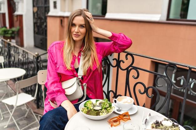 Portrait d'été en plein air d'une femme blonde joyeuse appréciant son délicieux brunch au café-terrasse de la ville.