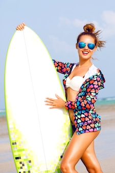 Portrait d'été en plein air de femme souriante en cours d'exécution avec planche de surfeur près de l'océan bleu