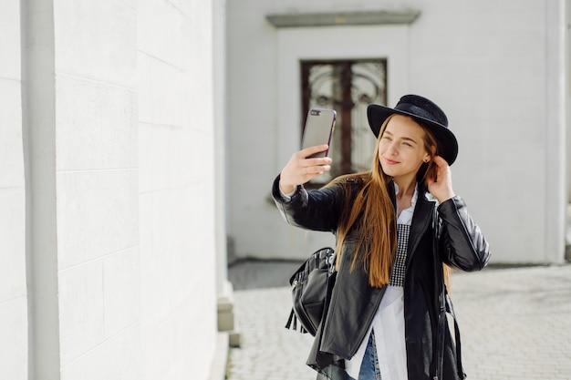 Portrait d'été en plein air de jeune fille élégante posée en journée ensoleillée sur rue avec téléphone