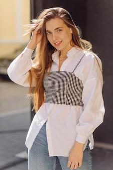 Portrait d'été en plein air de jeune fille élégante posée en journée ensoleillée sur la rue