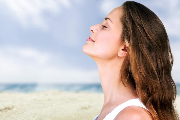Portrait d'été en plein air de jolie jeune femme heureuse souriante posant près de la mer