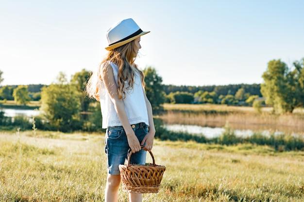 Portrait d'été en plein air de petite fille avec un panier de fraises
