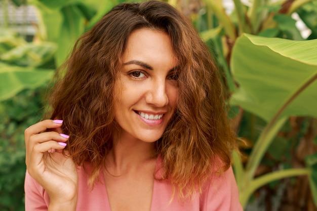 Portrait d'été en plein air de séduisante femme brune aux cheveux ondulés en robe rose posant sur tropical