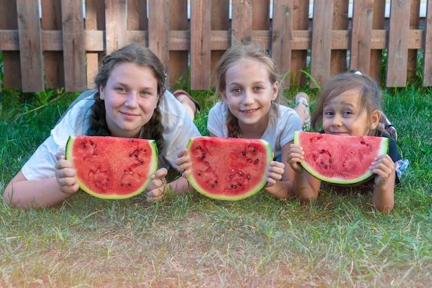 Portrait d'été de trois soeurs. enfants souriants en plein air. enfants avec pastèque. trois enfants souriants heureux mangeant de la pastèque dans le parc. concept de l'été.