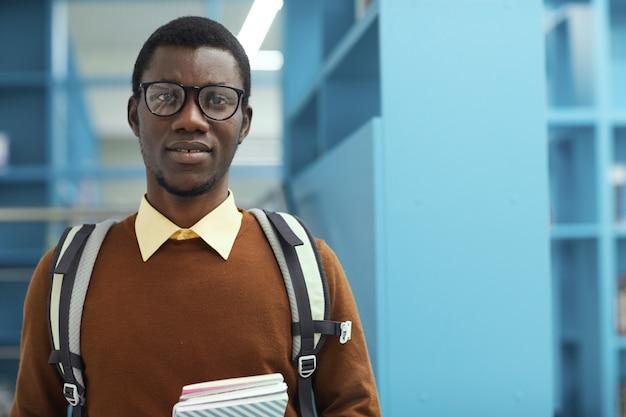 Portrait d'étudiant afro-américain dans la bibliothèque
