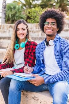 Portrait d'un étudiant afro souriant, assis avec sa petite amie à l'extérieur avec des livres