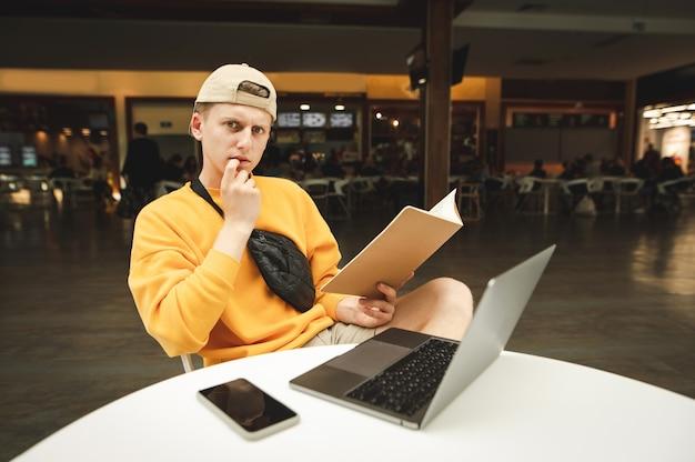 Portrait d'un étudiant attentionné assis à un bureau dans un centre commercial avec un bloc-notes
