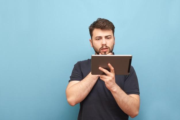 Portrait d'un étudiant avec une barbe debout sur le bleu et en utilisant internet sur un smartphone