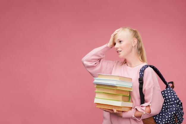Portrait d'un étudiant belle fille avec un sac à dos et une pile de livres dans ses mains