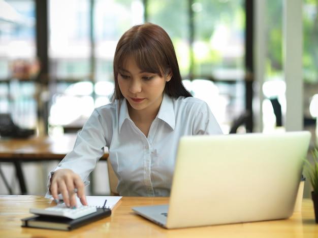 Portrait d'un étudiant calculant ses devoirs de mathématiques à une femme d'affaires de l'espace de coworking