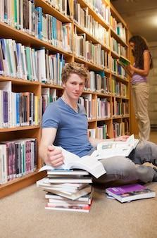 Portrait d'un étudiant faisant des recherches pendant que son camarade de classe est lu