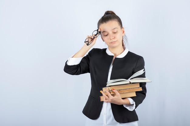 Portrait d'étudiant fatigué tenant des lunettes et des livres sur blanc.