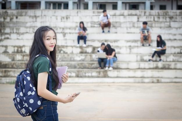 Portrait d'étudiant féminin tenant des livres. adolescents lycéens à l'extérieur