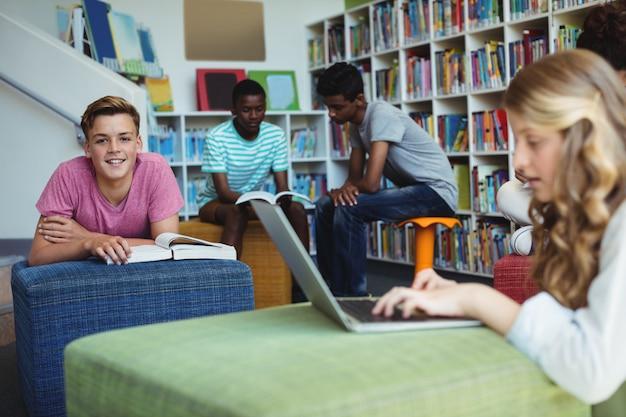 Portrait d'étudiant heureux qui étudie en bibliothèque