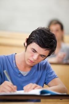 Portrait d'un étudiant prenant des notes