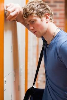 Portrait d'un étudiant solitaire appuyé sur un casier