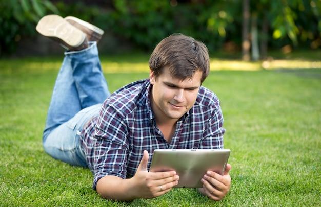 Portrait d'étudiant souriant à l'aide d'une tablette numérique sur l'herbe au parc