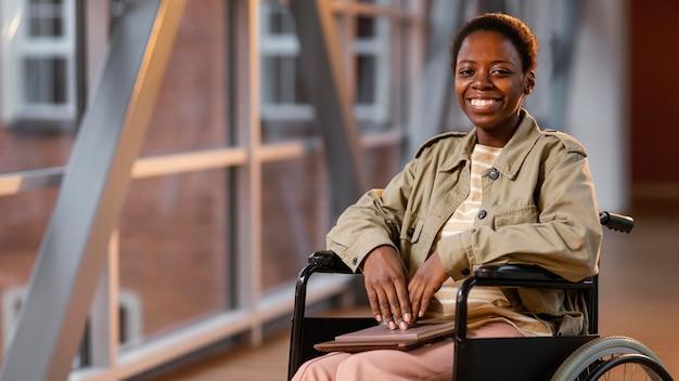 Portrait d'étudiant souriant dans un fauteuil roulant