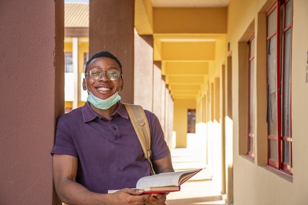 Portrait d'un étudiant souriant tenant un livre et souriant