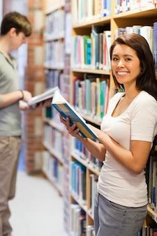 Portrait d'un étudiant souriant tout en tenant un livre