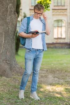 Portrait d'étudiant en train de lire à côté d'un arbre