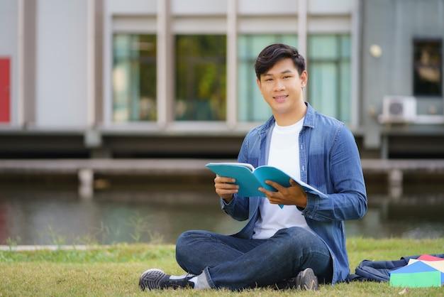Portrait d'étudiant universitaire homme asiatique aitting sur l'herbe dans le campus en regardant la caméra et le sourire et en lisant un livre dans le parc.