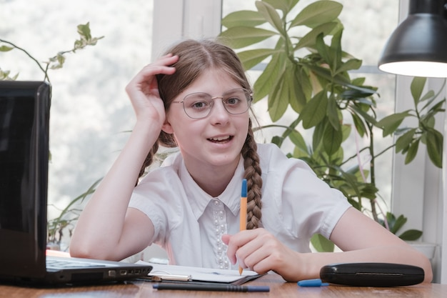 Portrait d'une étudiante appréciant l'apprentissage dans un bureau de coworking à l'aide d'un ordinateur portable pour la recherche, pigiste lors de la création d'un projet de prise de notes à distance. notes de dessin concentrées de l'élève