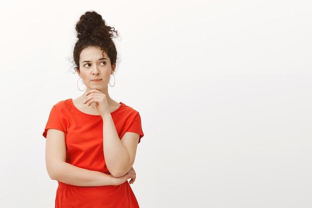 Portrait d'étudiante attrayante intense en difficulté en robe rouge décontractée élégante, croisant une main sur la poitrine et tenant la paume sur le menton
