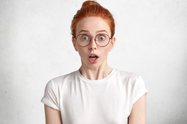 Portrait d'étudiante au gingembre surpris porte un t-shirt blanc et de grandes lunettes rondes, a la date limite pour passer le papier de diplôme