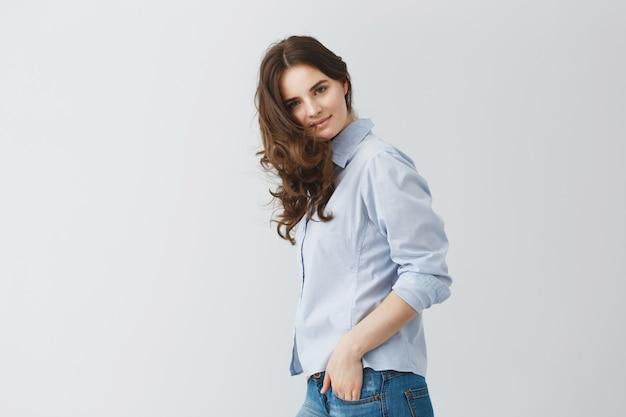 Portrait d'étudiante aux longs cheveux ondulés foncés, tenant les mains dans les poches avec une expression de visage calme et heureuse.
