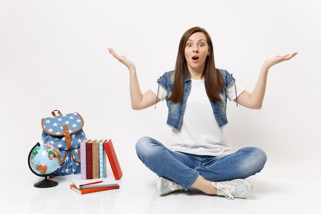 Portrait d'une étudiante choquée avec la bouche ouverte dans des vêtements en denim écartant les mains assises près des livres d'école de sac à dos globe isolés sur un mur blanc