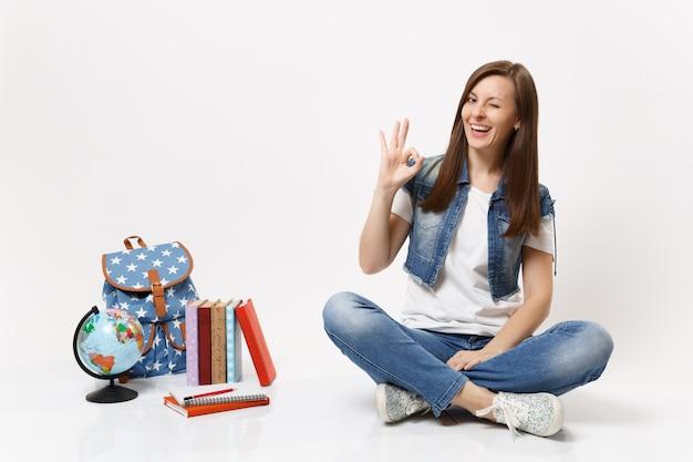 Portrait d'une étudiante drôle en vêtements en jean montrant le signe ok, clignotant assis près du globe, sac à dos, livres scolaires isolés sur mur blanc