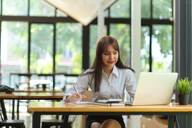 Portrait d'une étudiante faisant ses devoirs sur un ordinateur portable dans un espace de travail de café