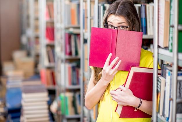 Portrait d'une étudiante fatiguée qui étudie avec des livres à la bibliothèque