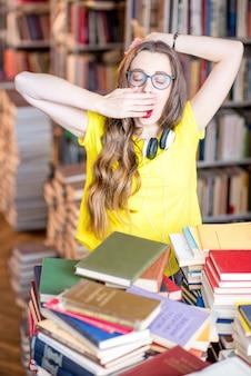 Portrait d'une étudiante fatiguée et stressée qui étudie avec des livres à la bibliothèque