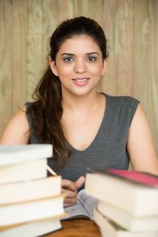 Portrait d'une étudiante heureuse assise au bureau