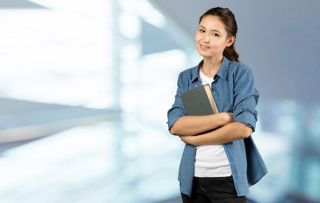 Portrait d'une étudiante heureuse fille ou femme avec des livres dans la bibliothèque