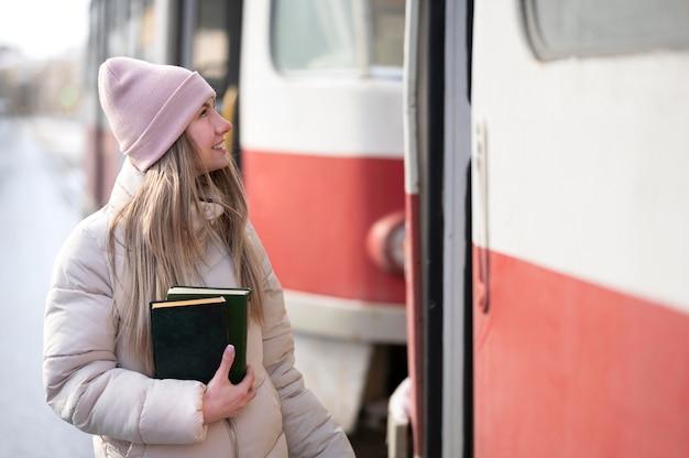 Portrait étudiante avec des livres à l'arrêt de tram