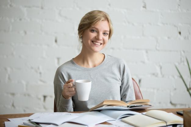 Portrait d'une étudiante souriante au bureau, tasse en main