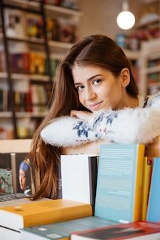 Portrait d'une étudiante souriante heureuse s'appuyant sur l'étagère du livre