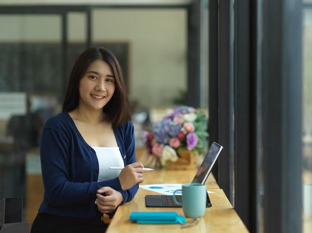 Portrait d'étudiante universitaire souriant à la caméra tout en faisant la cession avec tablette au café