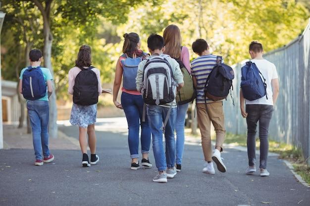 Portrait d'étudiants heureux debout avec backpackas sur route