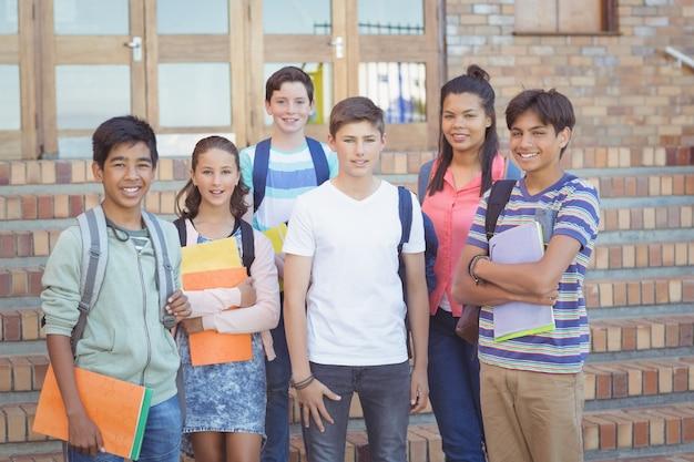 Portrait d'étudiants heureux debout avec des livres sur le campus